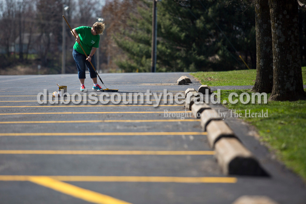 """Alisha Jucevic/The Herald <br /> <br /> Annette Witte of Ireland applied fresh paint to the parking lot outside St. Mary Catholic Church on Tuesday afternoon in Ireland. Witte works with the church and when they saw the parking lines was starting to fade, she knew it was something they could fix themselves instead of hiring an outside company to help. """"The perfect opportunity to work outside,"""" she said. Temperatures reached the high seventies on Tuesday afternoon, but are expected to drop throughout the week."""