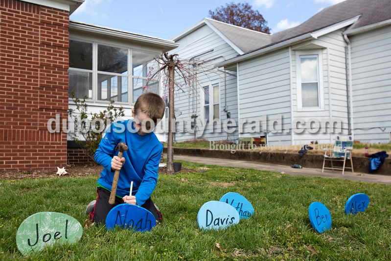Alisha Jucevic/The Herald <br /> <br /> Noah Buchanan of Evansville, 9, secured his easter egg in his grandmother's front yard on Monday afternoon in Jasper. Arlene Wuchner's daughters and grandchildren came over to her house Monday morning to help her clear and clean the landscaping around her home. When they had finished most of the yard work, they decided to put out their family Easter bunny. Wuchner said she bought the bunny 16 years ago when her first grandchild was born and for each new grandchild, she paints a new egg to put out with the bunny for Easter. This year there are 12 eggs.
