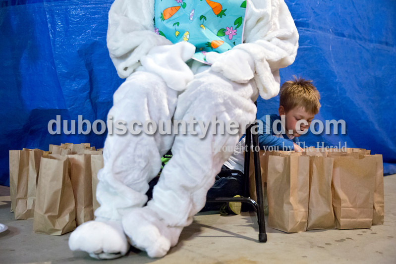 Sarah Ann Jump/The Herald<br /> Tucker Woolems of Dubois, 4, peaked in the bags of Easter eggs from his hiding spot behind the Easter Bunny's chair during Breakfast with the Easter Bunny sponsored by the Dubois Ruritan Club at Dubois Community Park on Saturday. Due to rain, the Easter egg hunt was cancelled and children received a bag of prize-filled eggs when they visited the bunny.