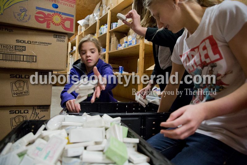 Sarah Ann Jump/The Herald<br /> Jasmine Leighty of Petersburg, 11, left, and sisters Sara, 15, and Emily Haas, 13, of Jasper, sorted toiletries at Helping His Hands Disaster Response warehouse in Vincennes on Tuesday. The donated toiletries will be used to make health kits for distribution to disaster victims.