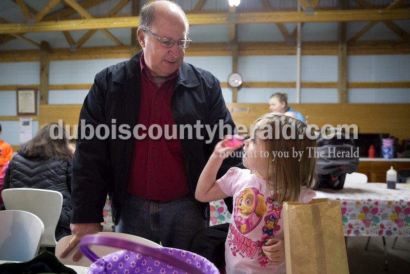 Sarah Ann Jump/The Herald<br /> Aubrey Hagen of Jasper, 4, shook an Easter egg as she tried to guess which prize was inside for her grandfather Stan Betz of Jasper during Breakfast with the Easter Bunny sponsored by the Dubois Ruritan Club at Dubois Community Park on Saturday.