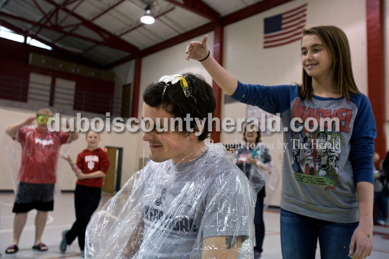 Alisha Jucevic/The Herald <br /> <br /> Southridge Middle School ended their week of fundraising for Riley Hospital for Children in Indianapolis with a pep rally and an egg roulette game. Eighth-grader Brianna Stasel smashed a raw egg on english teacher Aaron Wiles' head on Friday afternoon at the pep rally. Ten teachers entered their names and had to have at least $25 raised in their name, $50 for the principal, to play roulette. Seven teachers, including principal   Annette Altmeyer, raised enough to play. Throughout the week $2394.67 was raised, $243.94 of that from the roulette game.