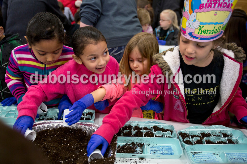 Alisha Jucevic/The Herald<br /> Fifth Street Elementary first-graders Guiselle Rivas Lovo, left, Yoselin Ayala, Ryleigh Opel and Kendall Corbin filled their cartons with dirt before planting seeds during a field trip to The Lodge on Friday morning on the south side of Jasper. The field trip was a partnership between Fifth Street's Wellness Committee and Memorial Hospital.