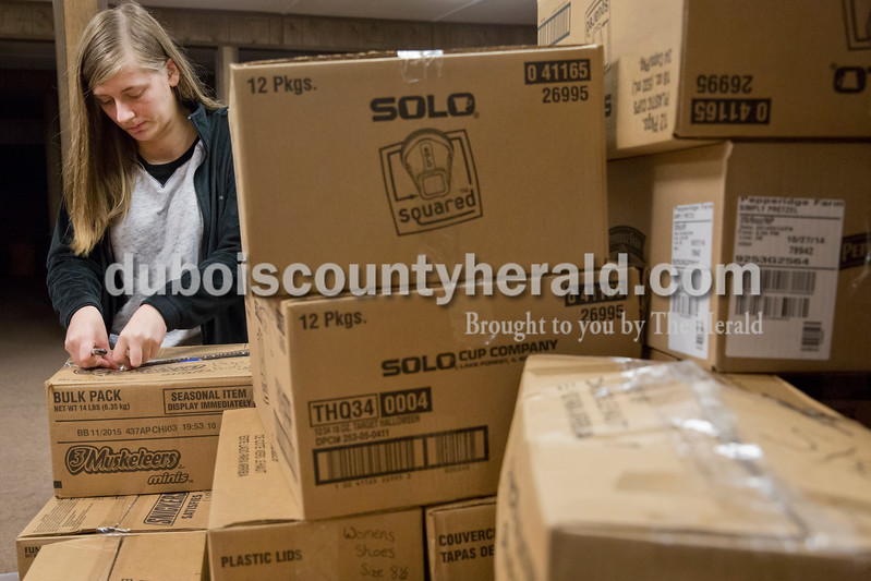 Sarah Ann Jump/The Herald<br /> Sara Haas of Jasper, 15, labeled boxes of clothing at Helping His Hands Disaster Response warehouse in Vincennes on Tuesday.