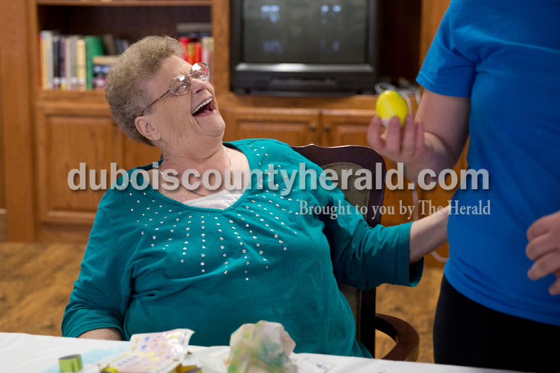 Sarah Ann Jump/The Herald<br /> Bernice Brosmer of Jasper laughed at the result of a dyed egg, held by volunteer Lily Morgan of Birdseye, 11, at Northwood Retirement Community in Jasper on Wednesday.