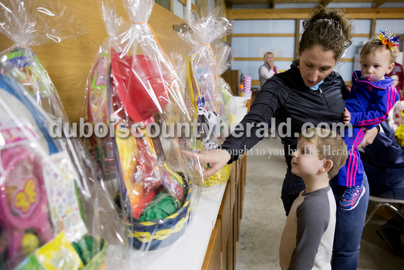 Sarah Ann Jump/The Herald<br /> Waylon Barker of Jasper, 5, listened as Erin Kalb of Dubois, holding her daughter Ashtyn, 1, explained his choice of prizes after having his name drawn during Breakfast with the Easter Bunny sponsored by the Dubois Ruritan Club at Dubois Community Park on Saturday.