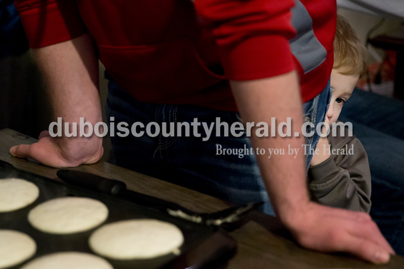 Sarah Ann Jump/The Herald<br /> Liam Terwiske of Dubois, 3, kept his eye on the Easter Bunny as he hid behind his father Joel, who was making pancakes, during Breakfast with the Easter Bunny sponsored by the Dubois Ruritan Club at Dubois Community Park on Saturday.