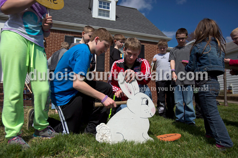 Alisha Jucevic/The Herald <br /> <br /> Will Weinzapfel, 12, left, and his cousin Andrew Gadlage, 16, both of Jasper, secured a wooden Easter bunny in their grandmother's front yard on Monday afternoon in Jasper. Arlene Wuchner's daughters and grandchildren came over to her house Monday morning to help her clear and clean the landscaping around her home. When they had finished most of the yard work, they decided to put out their family Easter bunny. Wuchner said she bought the bunny 16 years ago when her first grandchild was born and for each new grandchild, she paints a new egg to put out with the bunny for Easter. This year there are 12 eggs.