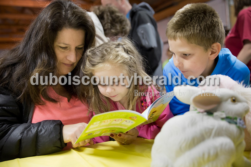 """Sarah Ann Jump/The Herald<br /> Jenny Lampert of Jasper, read the book """"Gus Grows a Plant"""" with her children Lexi, 5, and Caleb, 9, during Breakfast with the Easter Bunny sponsored by the Dubois Ruritan Club at Dubois Community Park on Saturday. Each of the approximately 70 children that attended received a children's book of their choice and a pencil."""