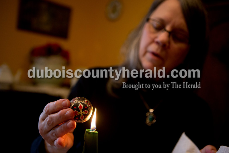 Ariana van den Akker/The Herald<br /> Anita Murphy of Dubois melted the beeswax off of a Ukrainian Easter egg to reveal its final design at her home on Monday morning. To make the eggs, called pysanky, beeswax is drawn onto the eggs with a special tool called a kistka and then the egg is dyed in layers as more beeswax is drawn on. Murphy learned the craft from a friend's Ukrainian grandmother.