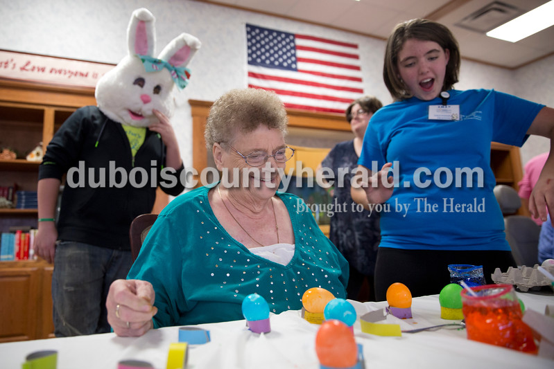 "Sarah Ann Jump/The Herald<br /> Bernice Brosmer of Jasper, center, reacted after volunteer Lily Morgan of Birdseye, 11, right, dropped an egg into the dye while volunteer Connor Wilson of Loogootee, 14, wore the head of an Easter bunny costume at Northwood Retirement Community in Jasper on Wednesday. ""We're just like kids,"" said Brosmer. ""We love to dye eggs!"""