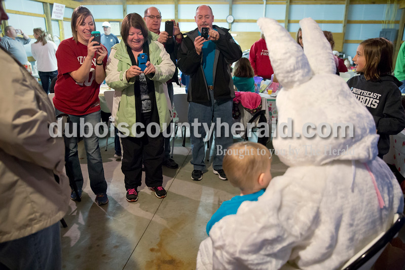 Sarah Ann Jump/The Herald<br /> Kamden Hagen, 1, and Aubrey Hagen, 4, sat with the Easter Bunny as their mother Jenna Hagen, left, and grandparents Linda Betz, Stan Betz and Don Dewig, all of Jasper, took photos during Breakfast with the Easter Bunny sponsored by the Dubois Ruritan Club at Dubois Community Park on Saturday.