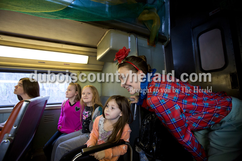 Sarah Ann Jump/The Herald<br /> Playing a munchkin, Kylie Schweikarth of Celestine, 15, entertained passengers June Stewart, 6, left, Alayna Nicholson, 8, and Olivia Lear, 7, all of Rockville, during the Wizard of Oz Train Ride on the French Lick Scenic Railroad on Friday.