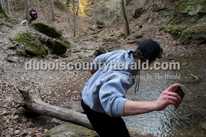 Carson Englert of Jasper, 17, skipped rocks in a pool of water below one of the waterfalls while hiking with Mariah Morgan of Birdseye, 18, on March 6. Dave Weatherwax/The Herald