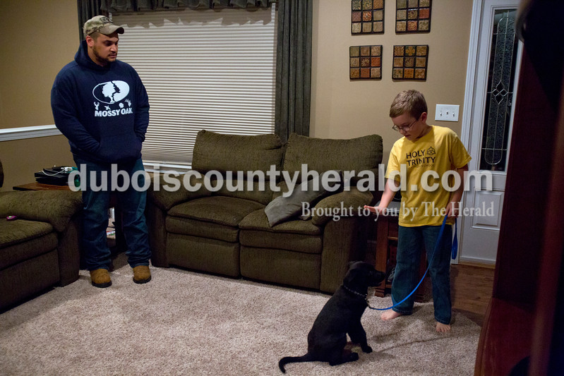 Alisha Jucevic/The Herald <br /> Tony Neal of Jasper works with Noah Lukemeyer, 10, and his family's new puppy at the Lukemeyer home on Feb 24 in Jasper. Neal is a former United States Air Force Military working dog handler and has almost 8 years of dog handling and training experience. Through his business, Pawzible Solutionz, Neal and his girlfriend Ali Brewer offer level 1 through 3 group and individual training, puppy school and a board and train service.