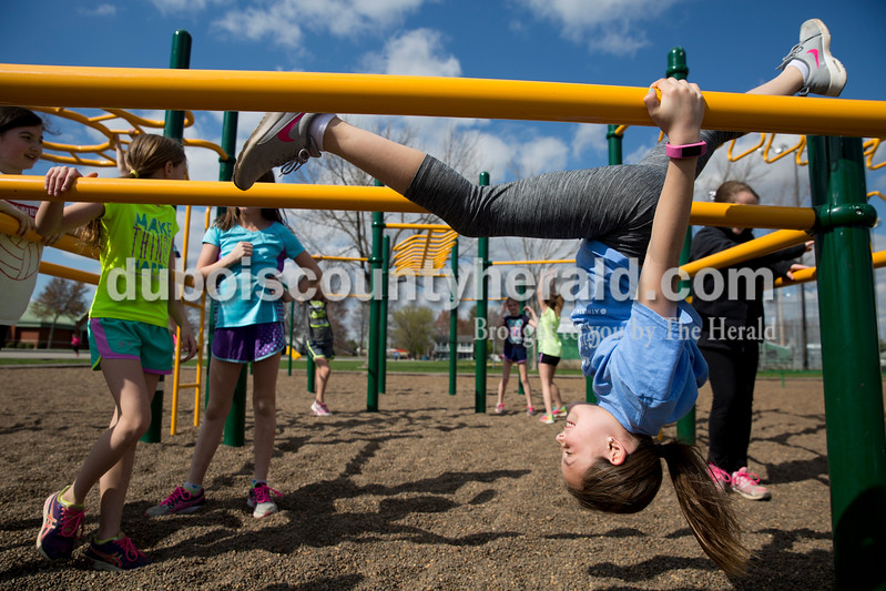 Sarah Ann Jump/The Herald<br /> Hannah Aull of Jasper, 9, hung on the bars on the playground at Ireland Elementary as she and her teammates took a break after running laps during Girls on the Run on Monday.