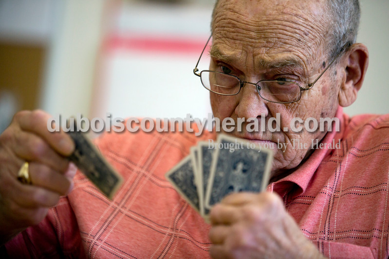 Ariana van den Akker/The Herald<br /> John Wirthwein of Huntingburg played a card during a euchre tournament at the Huntingburg Senior Center on Monday. The senior center has the tournaments twice a month. Wirthwein said he's been playing euchre for about 75 years.
