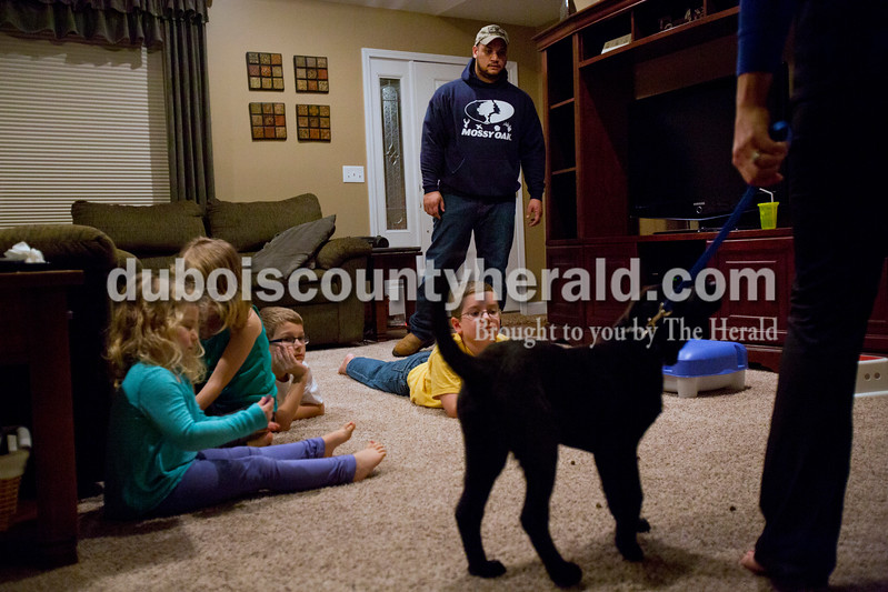 Alisha Jucevic/The Herald <br /> Tony Neal of Jasper, center, worked with the Lukemeyer Family's new puppy at their home on Feb 24 in Jasper. The Lukemeyer children, Ashley, 4, left, Abby, 6, Nate, 8, and Noah, 10, watch their mother, Anita, lead the dog past treats in the living room. Neal is a former United States Air Force Military working dog handler and has almost 8 years of dog handling and training experience.