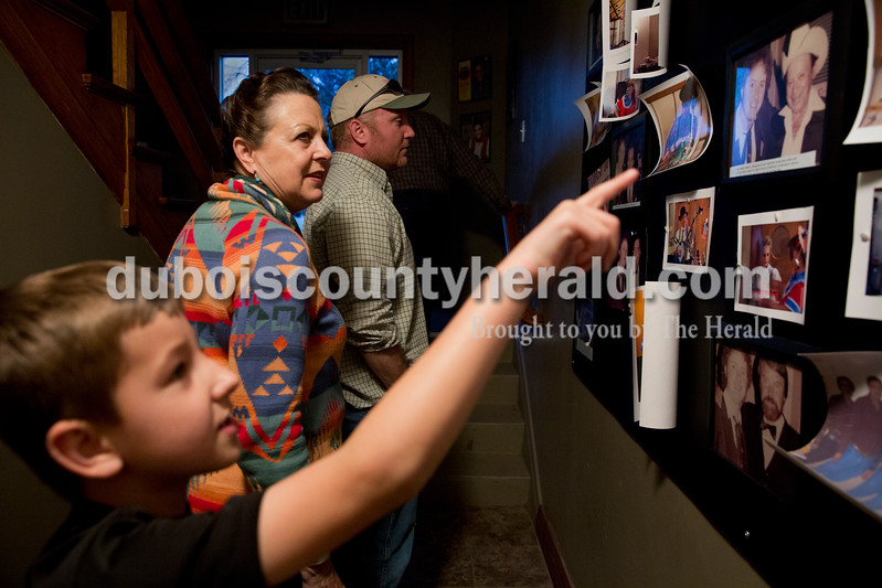 Sarah Ann Jump/The Herald<br /> Logan Katterhenry of Huntingburg, 7, left, Debby McQueen of Cincinnati, Ohio, and Travis McQueen of Jasper looked at old photos of the performers on display during intermission of Saturday's show at the Huntingburg Opry Hall.