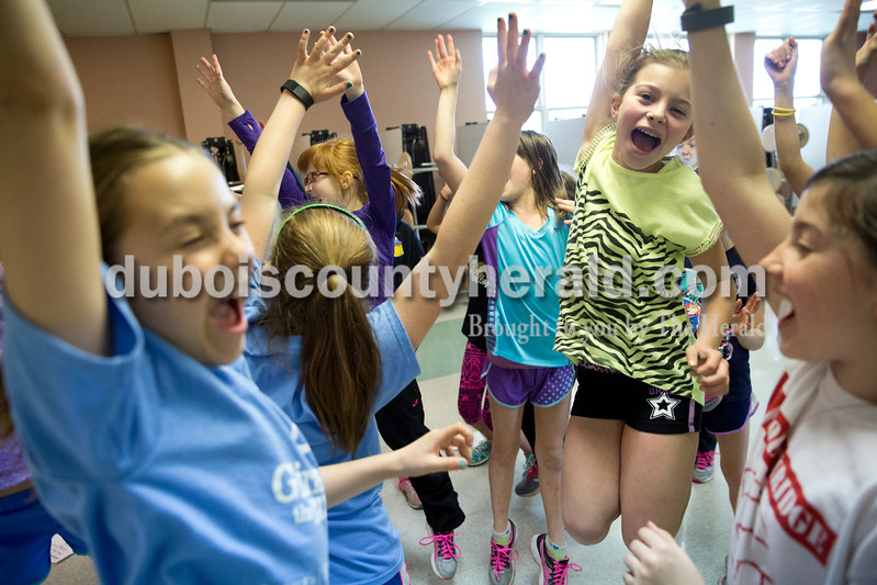 "Sarah Ann Jump/The Herald<br /> Girls on the Run participants jump and cheer as they receive an ""Energy Award"" during a session on Monday. At the close of every Girls on the Run session, participants acknowledge each other's accomplishments by nominating one another and having the group do a particular move with the nominees in the center of the circle. In this case, the entire team was nominated together."