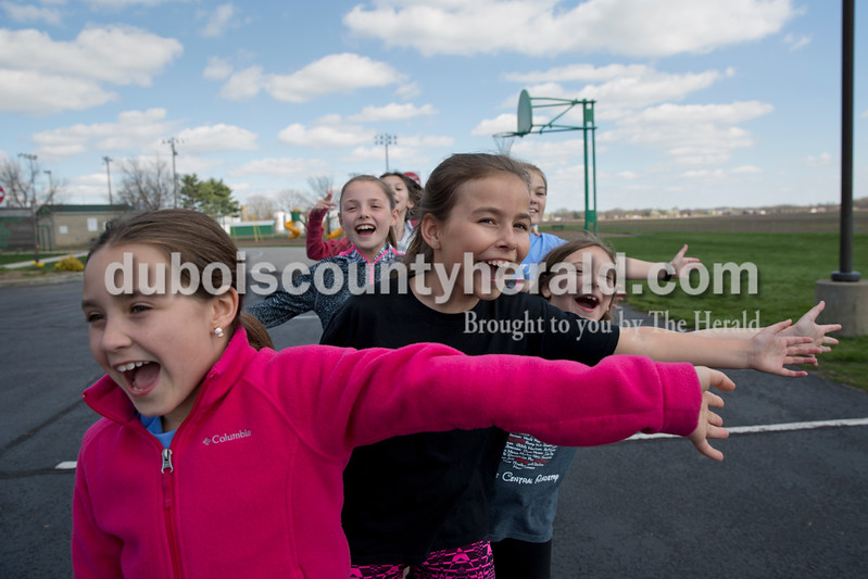 Sarah Ann Jump/The Herald <br /> Girls on the Run participants, from left, Hannah Aull, 9, Ally Wigand, 11, Hannah Levy, 11, and Kalea Uebelhor, 9, all of Jasper, cheered for their teammate Anna Sermersheim of Jasper, 10, ready to give high-fives as she ran back, during a session on Tuesday at Ireland Elementary School. The relay-style activity quizzed them on their lesson about bullying and served as a warm up before running laps.