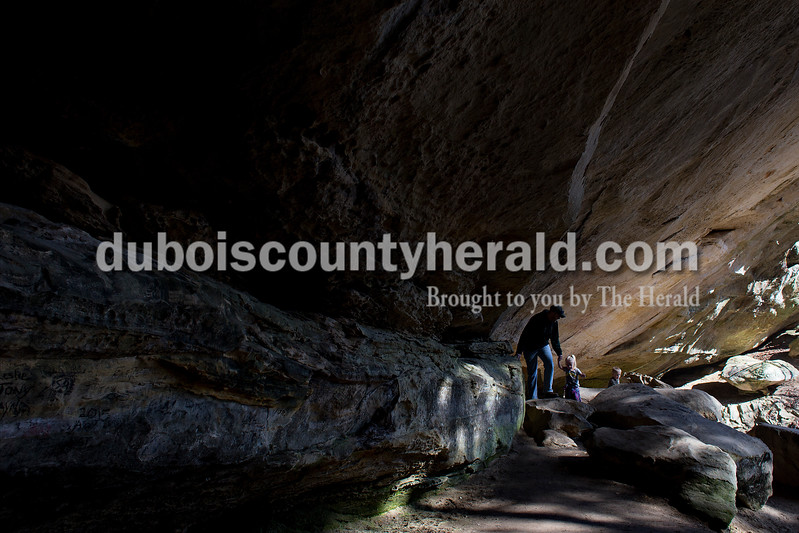 Mike Peterson of Scottsburg helped his daughter, Julia, 4, and son, William, 6, maneuver around and over boulders underneath Hemlock Cliffs' largest overhang March 6. Dave Weatherwax/The Herald