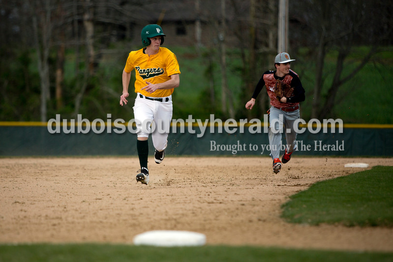 Forest Park's David Lusk ran to third base with Crawford County's Gavin Coleman in pursuit during Wednesday's game in Ferdinand. The Rangers won 2-0. Ariana van den Akker/The Herald