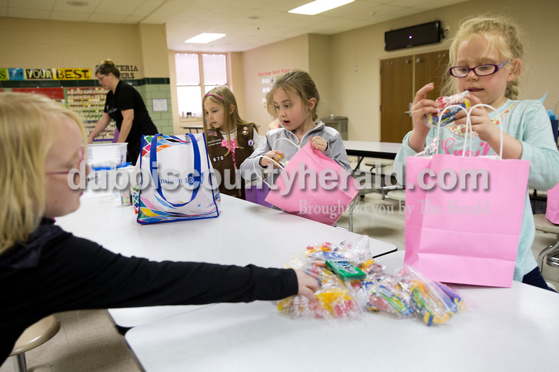 Sarah Ann Jump/The Herald<br /> Rhyanna Allen of Ferdinand, 7, left, Isabelle Meyer of Jasper, 8, Ariana Monroe of Jasper, 8, and Lillie Campbell of Ferdinand, 7, added items to gift bags for chemotherapy patients at Memorial Hospital during Girl Scout Troop 670's meeting at Fifth Street Elementary School in Jasper on Monday.