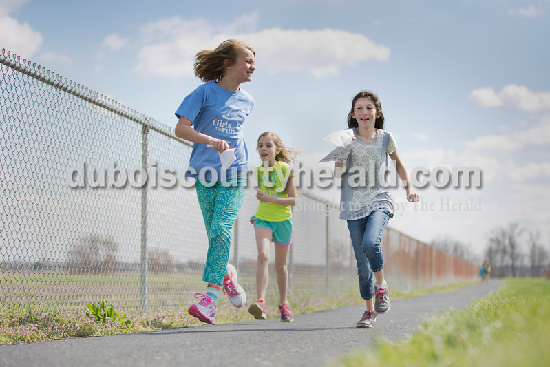 Sarah Ann Jump/The Herald<br /> Madelyn Day of Jasper, 10, left, Allie Freyberger of Jasper, 10, and Rileigh Verkamp of Ireland, 12, ran together during Girls on the Run at Ireland Elementary on Monday. As they ran, they completed a worksheet about bullying. Before each lap, they would read a question and discuss it as they ran, recording their answers after the lap. Every  Girls on the Run session includes a lesson addressing issues that girls in third through fifth grades face. The program also aims to build confidence through fitness and at the end of their season the girls will run a 5k.