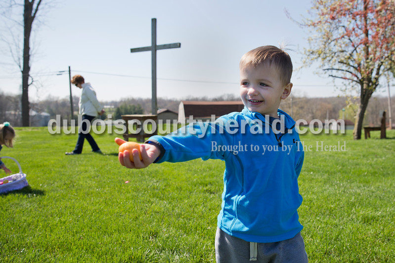Sarah Ann Jump/The Herald<br /> Jackson Leinenbach, 3, held out an egg he found to show his mother during Saturday's Easter egg hunt sponsored by the Haysville Ruritan Club at St. Paul Lutheran Church in Haysville.