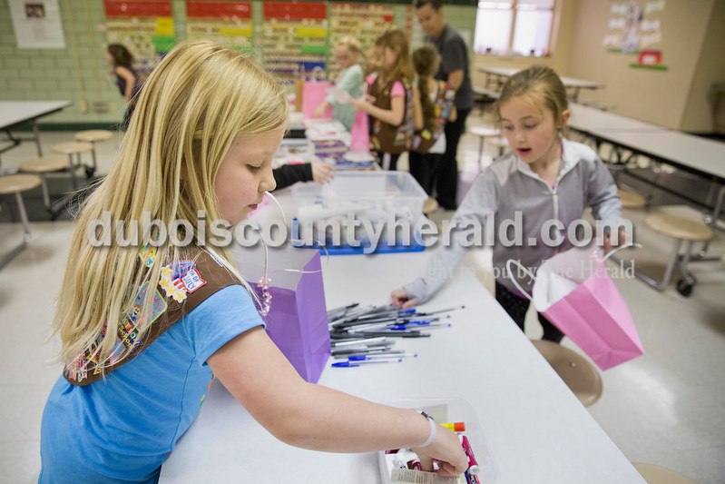 Sarah Ann Jump/The Herald<br /> Ellie Underwood of Jasper, 8, left, selected a lip balm and Ariana Monroe of Jasper, 8, grabbed a pen to add to gift bags for chemotherapy patients at Memorial Hospital during Girl Scout Troop 670's meeting at Fifth Street Elementary School in Jasper on Monday. As a service project, the Girl Scouts gathered donated items and assembled gift bags to help patients stay comfortable and entertained during treatments.