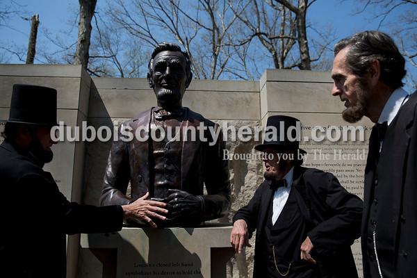 Charles Kleiner of Cincinnatio, Ohio compared his hand to the those of    a twice-life-size bronze bust of Abraham Lincoln as he talked with Jim Sayre of Lawrenceburg, Ky. and John Mansfield of Nashville, Tenn. at Bicentennial Plaza in Lincoln State Park in Lincoln City on April 15.