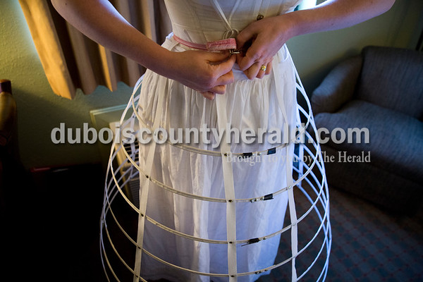 Laura Keyes of Freeport, Ill. put on her steel-hooped cage crinoline as she got dressed for the gala, where she portrayed Abraham's wife, Mary Todd Lincoln, on April 16. Under her silk dress, she wore a chemise, pantalettes, a steel and linen corset, stockings, a modesty petticoat, a cage crinoline and two additional petticoats.
