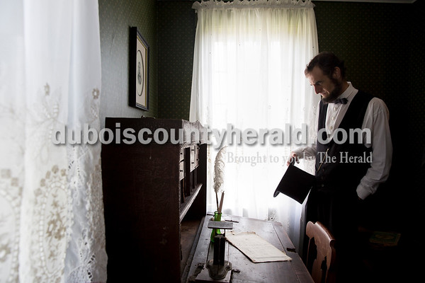 """Kevin Wood of Oak Park, Ill. looked over Squire Samuel Pate's desk at the Pate House in Lewisport, Ky. on April 16. In 1822, at that desk in that room, Squire Pate presided over Lincoln's first trial in which Lincoln defended himself against charges of operating a ferry across the Ohio River without a license. Squire Pate sided with Lincoln in the case. Wood, dressed as Lincoln, said being at that desk made him think about what it would have been like to be 18-year-old Lincoln defending himself for the first time. """"What if the squire ruled against him?"""" thought Wood. """"Would that have turned him off from the law or was he the type of person that would have become more determined to learn law? I like to think he's the latter."""""""