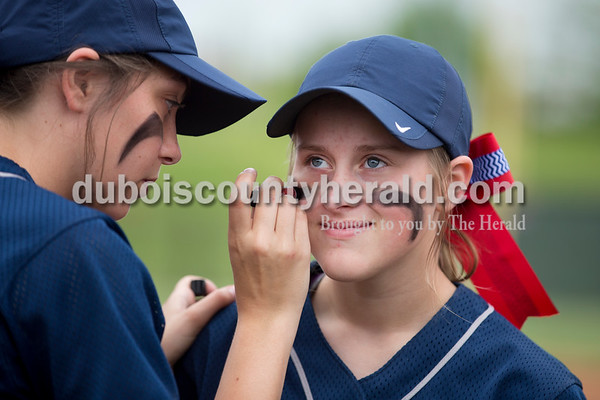 Heritage Hills' Haley Begle applied eye black to Mariah Zoglman's face before Friday's game at Southridge High School in Huntingburg. The Patriots beat the Raiders 9-3. Sarah Ann Jump/The Herald