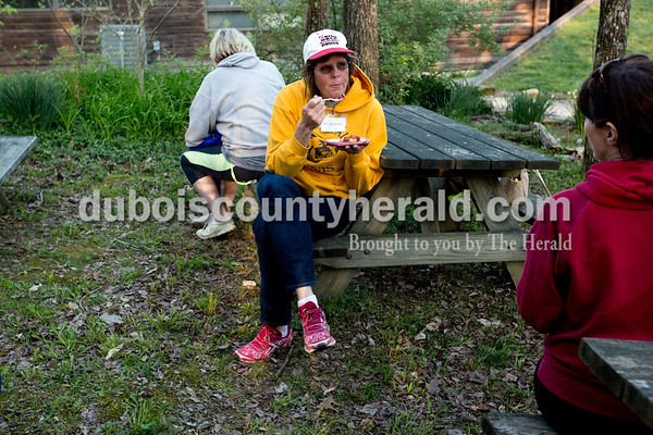 Ariana van den Akker/The Herald Angela Geiser of Evansville blew on a bite of cherry cobbler fresh from a dutch oven during a dutch oven cooking class on Saturday during the Women's Wilderness Weekend event at Patoka Reservoir.
