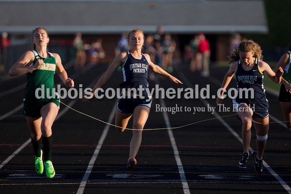 Heritage Hills' Jenna Burns, right, Heritage Hills' Kerragan Mulzer, center, and Wood Memorial's Ashlyn Morgan, left, crossed the finish line at the end of the 100-meter dash at Thursday's Southridge Invitational in Huntingburg. Morgan placed first, Burns placed second and Mulzer placed third. Heritage Hills picked up second place in the invitational behind Perry Central, while the host Southridge claimed third and Northeast Dubois took seventh of eight teams.    Alisha Jucevic/The Herald