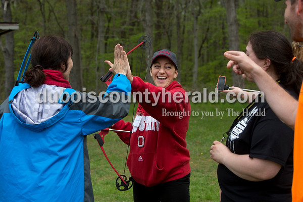 Ariana van den Akker/The Herald Billie Jo Brown of Newburgh, center, got a high five from Stephanie Criswell of Bloomington, left, after Brown hit a balloon target during an archery class on Saturday as part of the Women's Wilderness Weekend event at Patoka Reservoir.