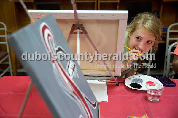 Sarah Ann Jump/The Herald Southridge High School senior Kathryn Brewer of Huntingburg, 18, peered around her painting to look at the sample painting made by Nicole McClain during a seniors painting night at Teen Outback in Huntingburg on Wednesday.