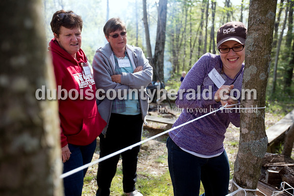 Ariana van den Akker/The Herald Crystal Buehler of Huntingburg tugged on a rope to make it as taught as possible while practicing how to make the top of a shelter during a survival skills class on Saturday during the Women's Wilderness Weekend event at Patoka Reservoir. Marlene James of Leopold, left, and Barbara Beckman of Lanesville watched.