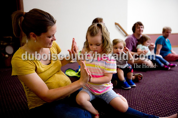 Ariana van den Akker/The Herald Harper Showalter of Jasper, 2, felt her mother Marci's hands during a Tuneful Tots class on Tuesday evening at the family life center at the Church of the Nazarene in Huntingburg. The class for toddlers and their caregivers blends music, movement, storytelling and play.