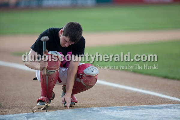 Sarah Ann Jump/The Herald Southridge's Harrison Steckler hammered the field cover in place during a weather delay at Tuesday's game against Washington High School at League Stadium in Huntingburg. The game was cancelled after the delay.
