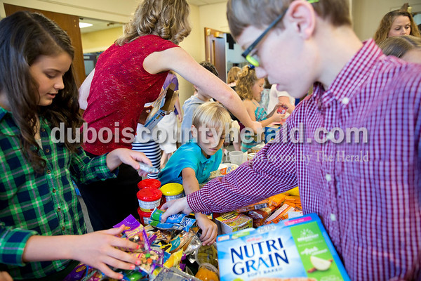 Sarah Ann Jump/The Herald Paige O'Neil, 11, left, Joel Levy, 8, and Robert White, 12, all of Jasper, sorted food they collected for the Backpack Buddies program at Shiloh United Methodist Church on Sunday morning.