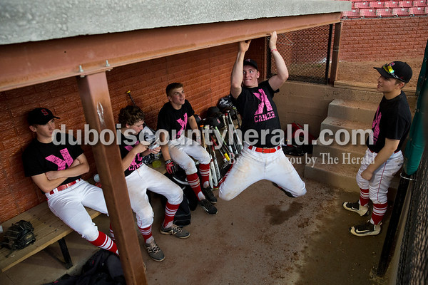 Sarah Ann Jump/The Herald Logan Seger, center, tried to move along the end of the dugout using only his upper body strength during a weather delay at Tuesday's game against Washington High School at League Stadium in Huntingburg. The game was cancelled after the delay.