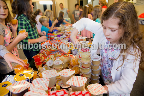 Sarah Ann Jump/The Herald Lea Rue of Jasper, 8, sorted food collected for the Backpack Buddies program at Shiloh United Methodist Church on Sunday morning.