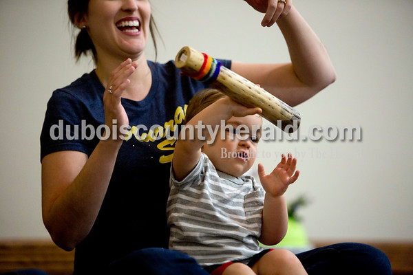 Ariana van den Akker/The Herald Owen Elrod of Jasper, 1, played with a rainstick while sitting in his mother Brooke's lap during a Tuneful Tots class on Tuesday evening at the family life center at the Church of the Nazarene in Huntingburg. The class for toddlers and their caregivers blends music, movement, storytelling and play.