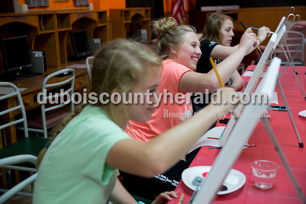 """Sarah Ann Jump/The Herald Southridge High School seniors Kathryn Brewer, left, Haley Barnett and Haili Estabrook, all 18 and of Huntingburg, painted the Southridge logo on canvasses at Teen Outback in Huntingburg on Wednesday evening. """"We wanted to do something special for the seniors,"""" said Teen Outback Youth Director April Blessinger, who planned the event. """"I thought it would make a great thing for them to keep from their senior year."""" Nicole McClain of The Modern Social sketched the logo on all of the canvasses and supplied the paints. They also served virgin strawberry daiquiris."""