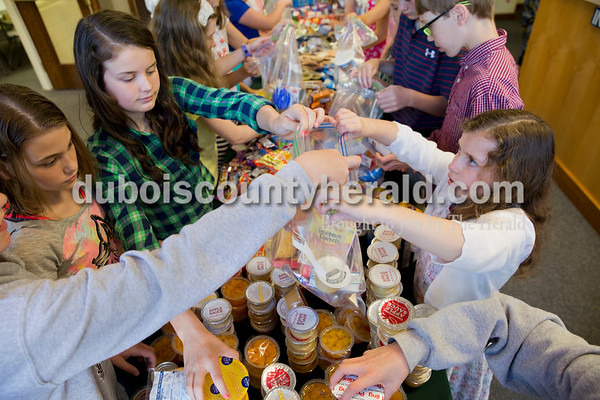 """Sarah Ann Jump/The Herald Kiersten Wagner, 12, left, Paige O'Neil, 11, and Lea Rue, 8, all of Jasper, filled a bag with food for the Backpack Buddies program at Shiloh United Methodist Church on Sunday morning.   The Backpack Buddies bags of food are distributed to kindergarten through fifth-graders in Dubois County each Friday to ensure they have food over the weekend. Myron Schmitt of Ireland founded the program at Shiloh United Methodist Church in 2014, and now works with several other churches and community groups to distribute approximately 250 bags of food to children each week. """"There's more need in the county than people realize,"""" he said. By getting students involved in the Backpack Buddies program, Schmitt hopes to raise awareness about childhood hunger and inspire children to be thankful for what they have.    Shiloh United Methodist Church members in pre-kindergarten through sixth-grades held a competition to see who could collect the most food. They then sorted the food and created an assembly line to complete the bags. Curriculum coordinator Sara Powell said that the service project worked into the Sunday School's curriculum about helping your neighbors. """"Part of being a good neighbor is being there for one another,"""" she said.   """"It feels awesome knowing that kids won't be hungry because I donated food,"""" said Hannah Levy of Jasper, 11. """"I feel special that I could make a difference.""""   """"I'm very thankful for everything I have,"""" said Kiersten Wagner of Jasper, 12. """"I think doing this is one step in changing the world."""""""