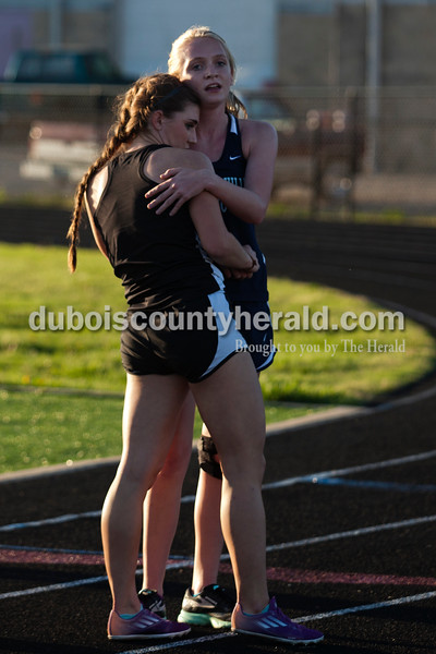 Heritage Hills' Caitlin Lueken hugged Southridge's Lauren Meyer after the 1,600-meter run during Thursday's Southridge Invitational in Huntingburg. Meyer placed first with a time of 5:45.3 and Lueken placed second with a time of 5:50.2. Heritage Hills picked up second place at the invitational behind Perry Central, while the host Southridge claimed third and Northeast Dubois took seventh of eight teams.   Alisha Jucevic/The Herald