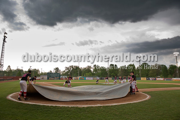 Sarah Ann Jump/The Herald The Southridge baseball team covers the field during a weather delay at Tuesday's game against Washington High School at League Stadium in Huntingburg. The game was cancelled after the delay.